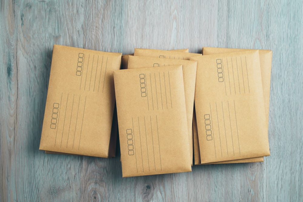 Kraft colored envelope mailers sitting on wood background