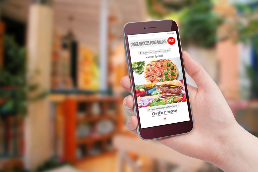 Female hand holding smartphone and ordering food via a restaurant app