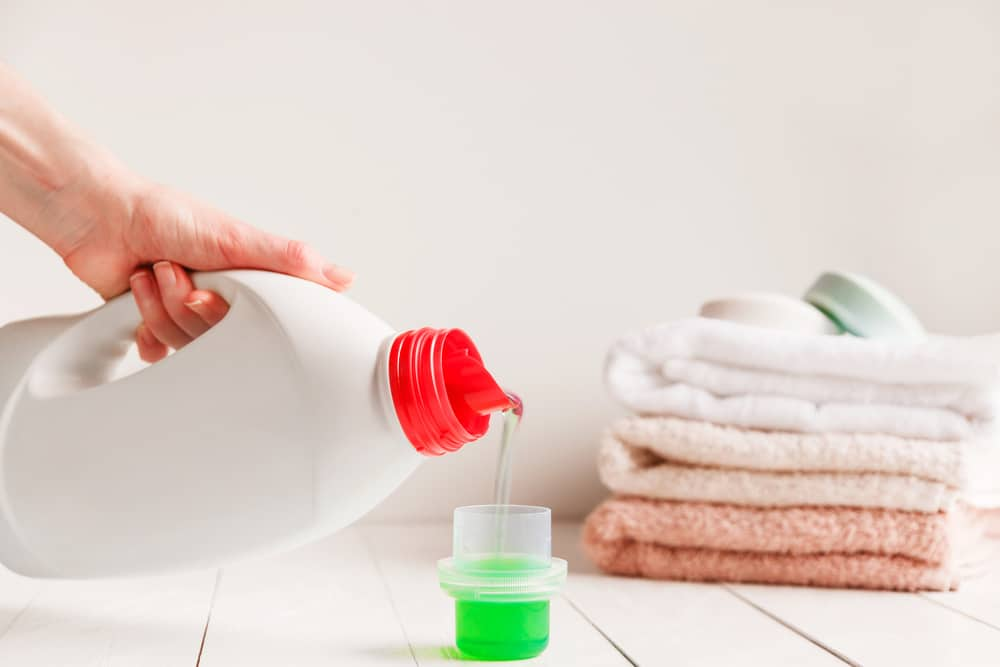 Laundry detergent being poured into measuring cup with a stack of towels in the background