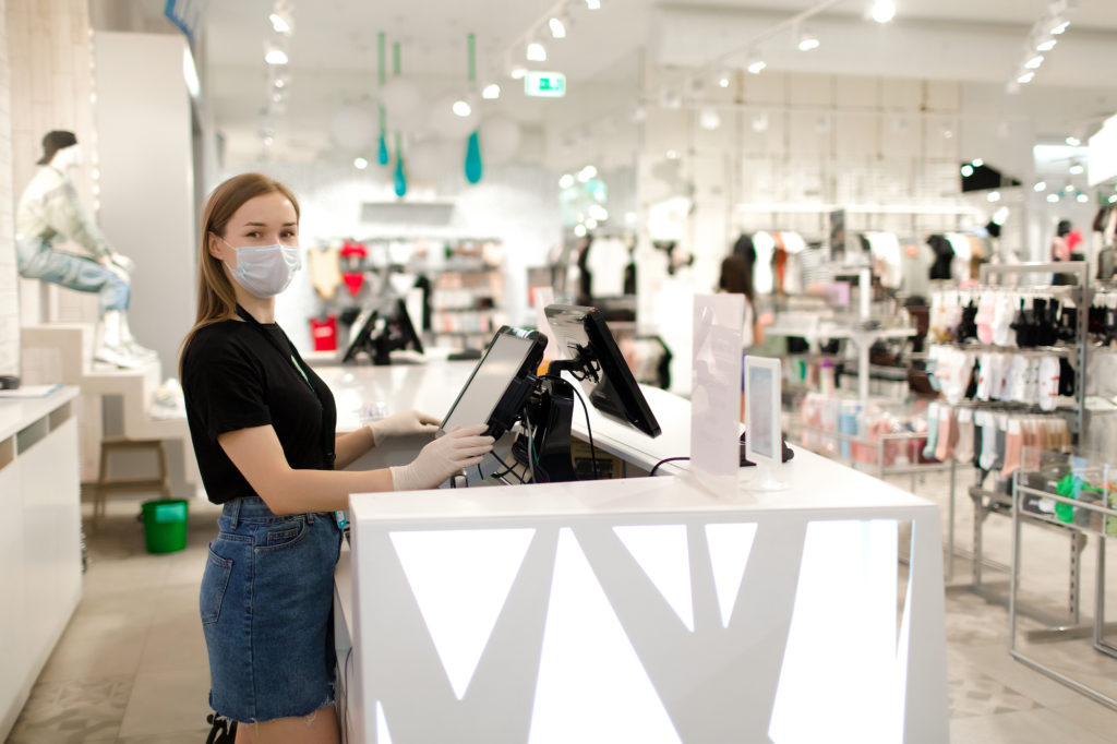 cashier at retail store standing at register, wearing a face mask