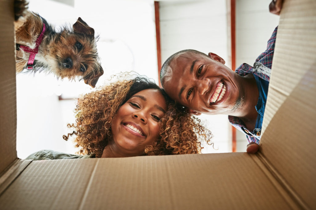 People and dog peering into a box